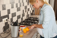 Preparing a healthy lunch. Beautiful pregnant woman cutting oranges for her breakfast Royalty Free Stock Image
