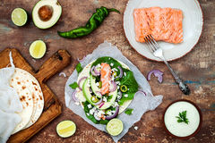 Preparing healthy lunch snacks. Fish tacos with grilled salmon, red onion, fresh salad leaves and avocado cilantro sauce. On vintage stone background. Recipe stock photos