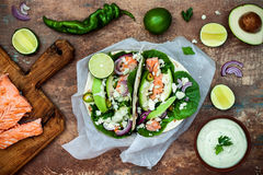 Preparing healthy lunch snacks. Fish tacos with grilled salmon, red onion, fresh salad leaves and avocado cilantro sauce Royalty Free Stock Images