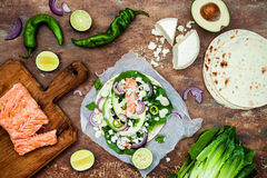 Preparing healthy lunch snacks. Fish tacos with grilled salmon, red onion, fresh salad leaves and avocado cilantro sauce Stock Photo