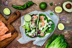 Preparing healthy lunch snacks. Fish tacos with grilled salmon, red onion, fresh salad leaves and avocado cilantro sauce. On vintage stone background. Recipe stock photography
