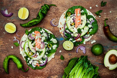 Preparing healthy lunch snacks. Fish tacos with grilled salmon, red onion, fresh salad leaves and avocado cilantro sauce royalty free stock image