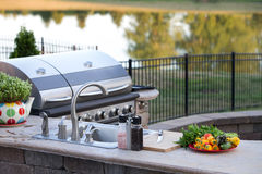 Preparing a healthy meal in an outdoor kitchen. Preparing a healthy summer meal in an outdoor kitchen with gas barbecue and sink on a brick patio overlooking a Stock Photo