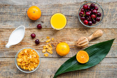 Preparing healthy summer breakfast. Muesli, milk, oranges, cherry, on wooden table background top view Stock Photography
