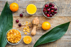 Preparing healthy summer breakfast. Muesli, oranges, cherry, juice on wooden table background top view Royalty Free Stock Image