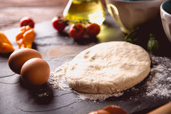 Preparing home pizza on wooden table with ingredients Stock Photos