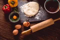 Preparing home pizza on wooden table with ingredients Stock Image