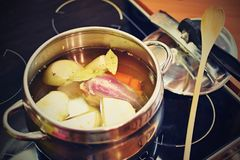 Preparing homemade chicken soup - broth. Pot on the stove in the kitchen with ingredients for cooking. Royalty Free Stock Photo