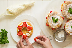 Preparing homemade choux pastry rings with cottage cheese cream and strawberries decorated mint leaves Royalty Free Stock Photo