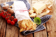 Preparing homemade Italian Pasta. With fresh egg noodles, parmigiano reggiano speciality cheese, basil and tomatoes on rustic wooden boards and a checked napkin Stock Image