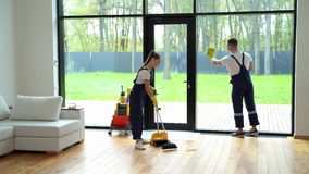 Young proffesional staff of cleaning service do spring-cleaning
