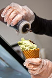 Preparing Ice Cream. Person wearing latex gloves preparing green tea ice cream on a cone Royalty Free Stock Photos