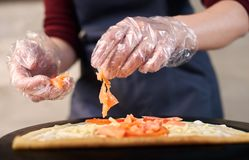 Preparing Italian pizza process. Chef hands in one-time gloves keeping salmon slices over pizza dough. Front focus view. Pizza chef hands in one-time gloves royalty free stock photos