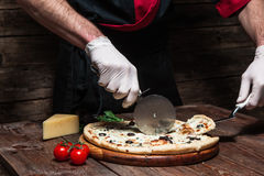 Preparing italian pizza by professional pizzaiolo. Culinary master class. Italian cuisine. Chef cutting slice of tasty fresh pizza on rustic wooden table Royalty Free Stock Photography