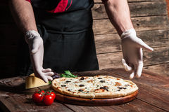 Preparing italian pizza by professional pizzaiolo. Culinary master class. Italian cuisine. Cooking and decorating delicious pizza from professional chef Stock Photography