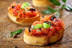 Preparing Italian tomato bruschetta. Preparing delicious Italian tomato bruschetta with chopped vegetables, herbs and oil on grilled or toasted crusty baguette Stock Photo