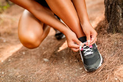 Preparing For A Jog. Close-up of a unrecognizable female person tying her sneakers in the pine forest Royalty Free Stock Images