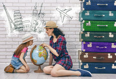 Preparing for the journey. Happy family preparing for the journey. mother and daughter looking at a globe and choose a country to travel Stock Images