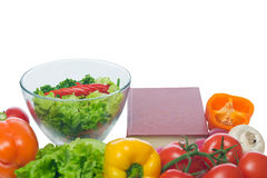 Preparing a low-calorie dish prescription. Book of recipes and vegetables on a white Royalty Free Stock Photos