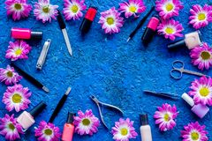 Preparing for manicure. Tools and nail polishes on blue background top view copyspace Stock Photography