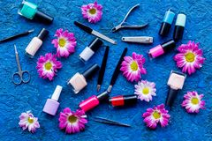 Preparing for manicure. Tools and nail polishes on blue background top view Stock Photos