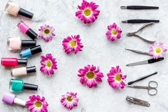 Preparing for manicure. Tools and nail polishes on grey background top view Stock Photo