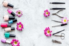 Preparing for manicure. Tools and nail polishes on grey background top view copyspace Stock Photography