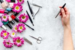 Preparing for manicure. Woman hand with manicure tool on grey background top view copyspace Royalty Free Stock Image