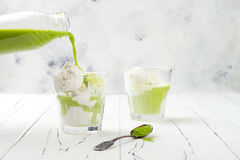 Preparing matcha green tea affogato with vegan coconut ice cream. royalty free stock images