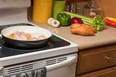 Preparing a meal at home. With fresh veggies and fried chicken Stock Images