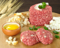 Preparing Meatball. With ingredients, such as egg, ground meat, dried bread, onions on wooden board (Selective Focus, Focus on raw meatballs Royalty Free Stock Photography