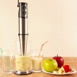 Preparing milkshake with fresh fruits in blender Stock Photos