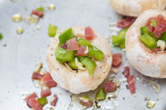 Preparing mushrooms stuffed with ham and pepper Stock Photography