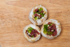 Preparing mushrooms stuffed with ham and pepper Stock Images