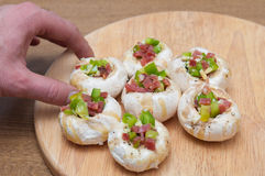 Preparing mushrooms stuffed with ham and pepper Royalty Free Stock Photography