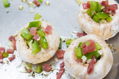 Preparing mushrooms stuffed with ham and pepper Royalty Free Stock Photo