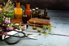 Preparing natural medicine, healing herbs, scissors and apotheca. Ry bottles on rustic blue painted wood with copy space, vintage style, selected focus Royalty Free Stock Photos
