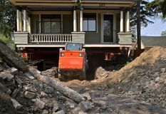 Preparing for a new foundation on a huge old house. A house under foundation repair rests on strong girders as a backhoe removes concrete and dirt from stock photos