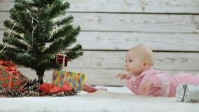 Preparing for the new year. Baby in pink for Christmas and New year background. Newborn girl lying under a decorated Christmas tree. The kid is considering a stock footage