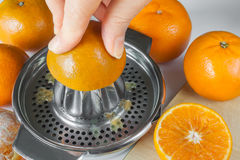 Preparing Of Mandarin Juice, Hands Squeeze Juice On A Manual Juicer Royalty Free Stock Photo