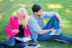 Preparing for the offset. Girl-student and male student holding. A laptop and textbooks and look aside while sitting on the grass near the campus of the Stock Image