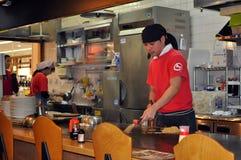 Preparing okonomiyaki. A cook in an okonomiyai restaurant preparing an order of Hiroshima style okonomiyaki Stock Photos