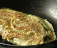 Preparing omelete. Frying omelete with herbs at home stock photo
