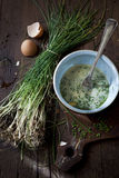 Preparing an omelette with fresh beaten eggs and wild chives on bowl Stock Photography