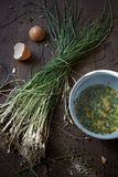 Preparing an omelette with fresh beaten eggs and wild chives on bowl Royalty Free Stock Photos