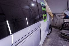 Preparing for painting a silver bus in a body repair shop in a s stock photography