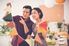 Preparing for party. Vietnamese couple deciding where to put garland when preparing for party Stock Photo