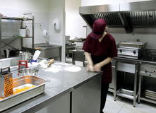 Preparing pastry in a restaurant kitchen. Female worker is preparing pastry in a commercial kitchen Royalty Free Stock Photography