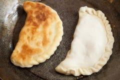 Preparing patty on frying pan Stock Images