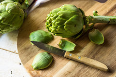 Preparing and peeling fresh artichoke for cooking, scattered green petals, cutting board, knife. Close up Royalty Free Stock Photo